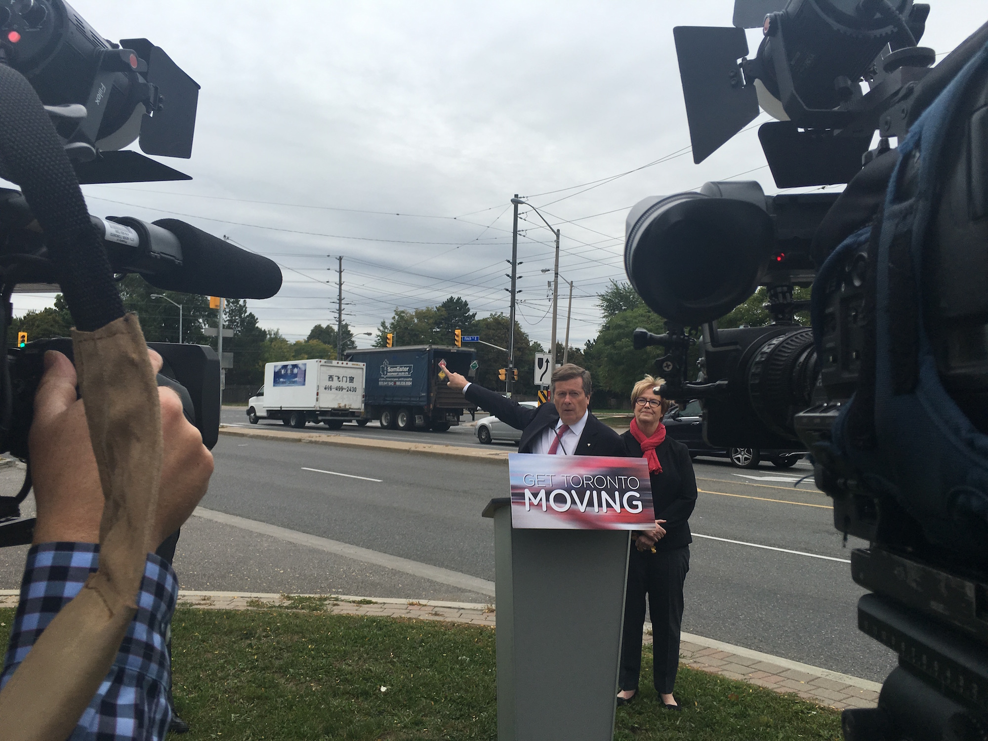 10:36 a.m., Monday, Sept. 26, 2016. City Councillor Shelley Carroll (right) stands behind Mayor John Tory as he points to traffic signals at Victoria Park and Finch Ave. East at a traffic improvements announcement.