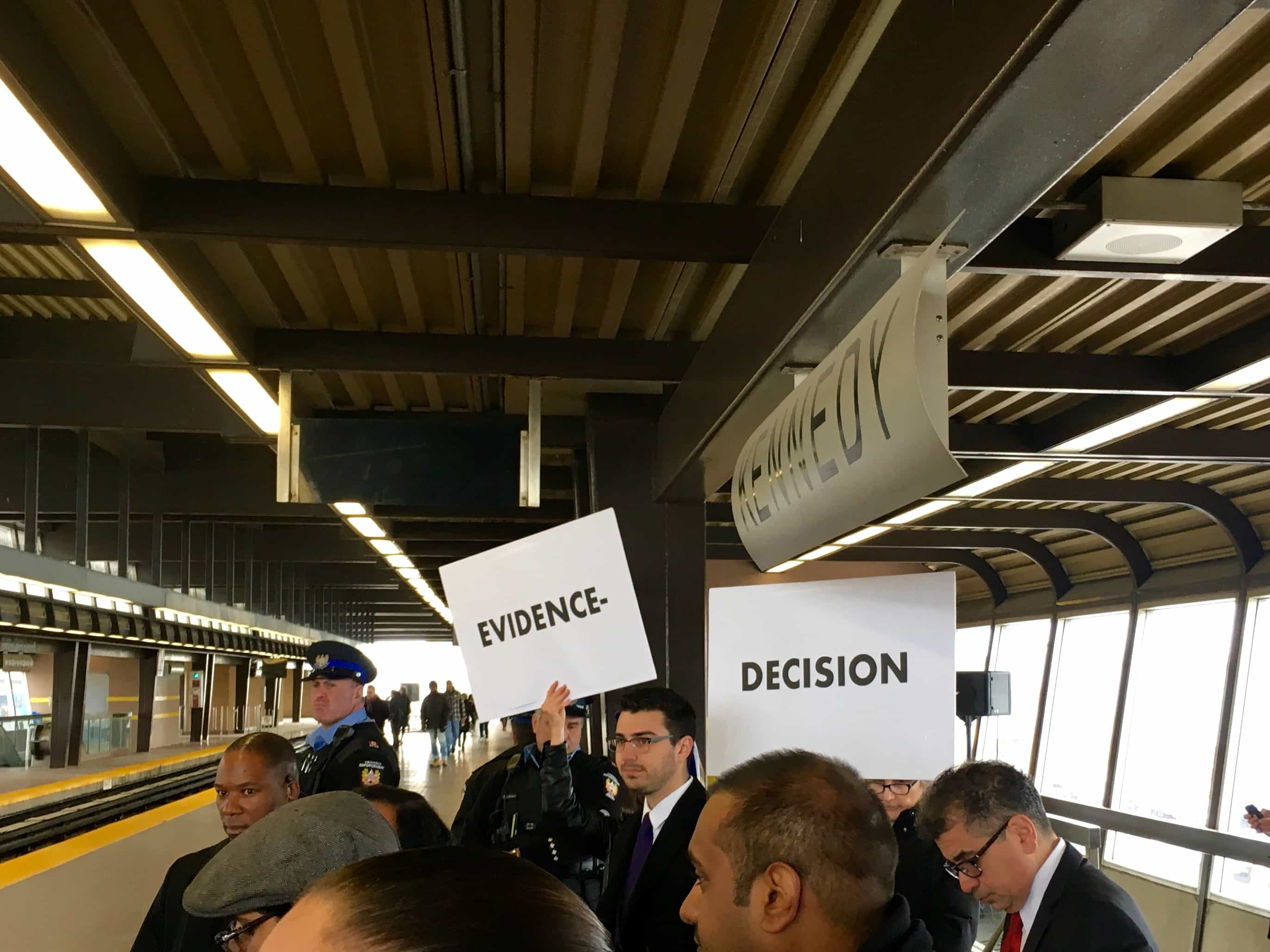 """10:18 a.m. Feb. 28, 2017. Two representatives from the group TTC Riders hold large signs up at Kennedy station Tuesday morning. Mayor John Tory met reporters to speak about the latest report to be considered before Executive Committee next week. """"This Scarborough shuffle here at Kennedy station has to come to an end,"""" Tory said. """"It is scandalous that people playing politics against the will of every democratic chess that we've had, has slowed the city down from getting Scarborough the transit that it needs in order to spur jobs and economic development."""""""
