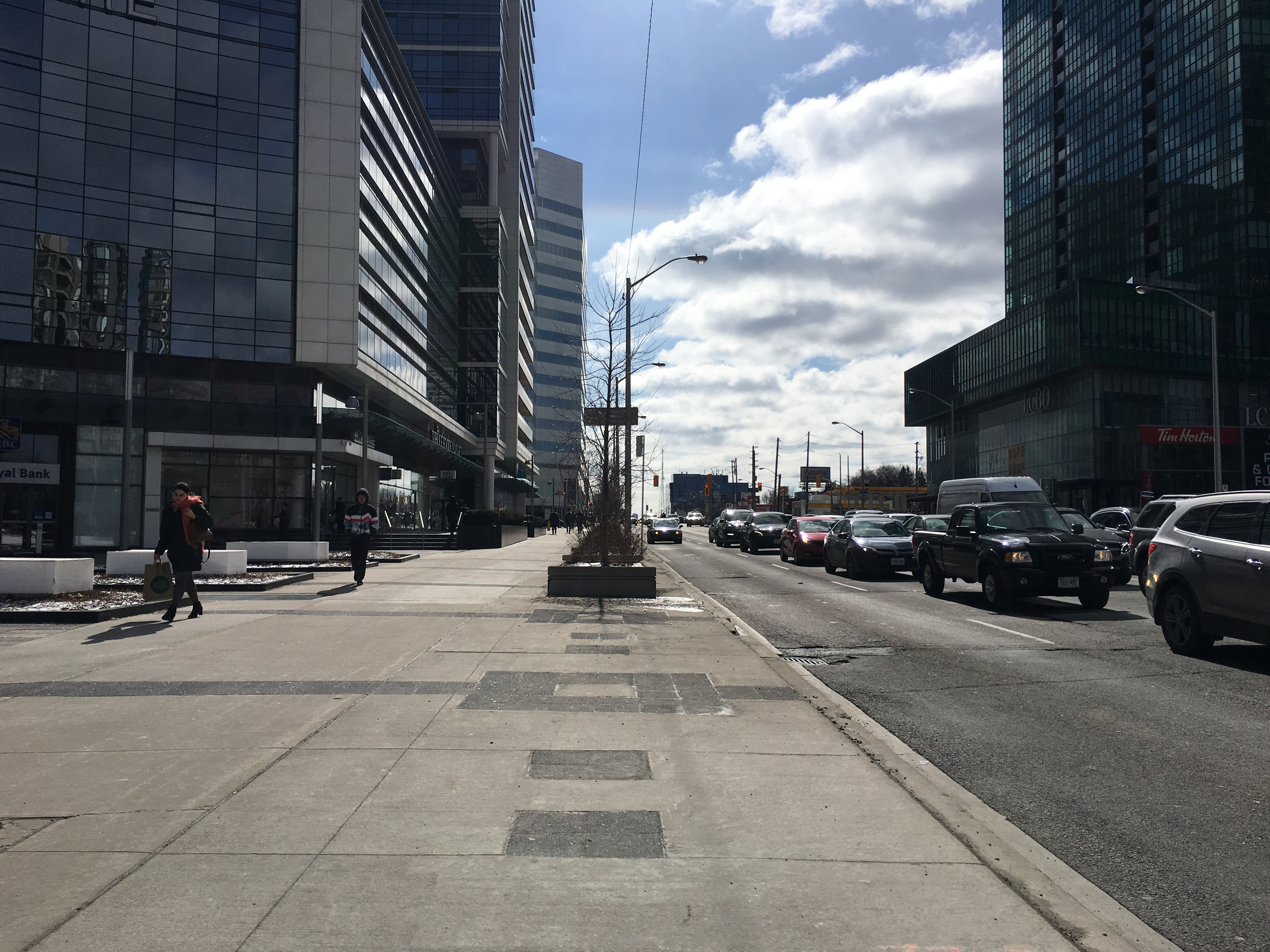12:01 p.m., March 2, 2018. Traffic builds up on Yonge Street near Sheppard Avenue, next to wide sidewalks.