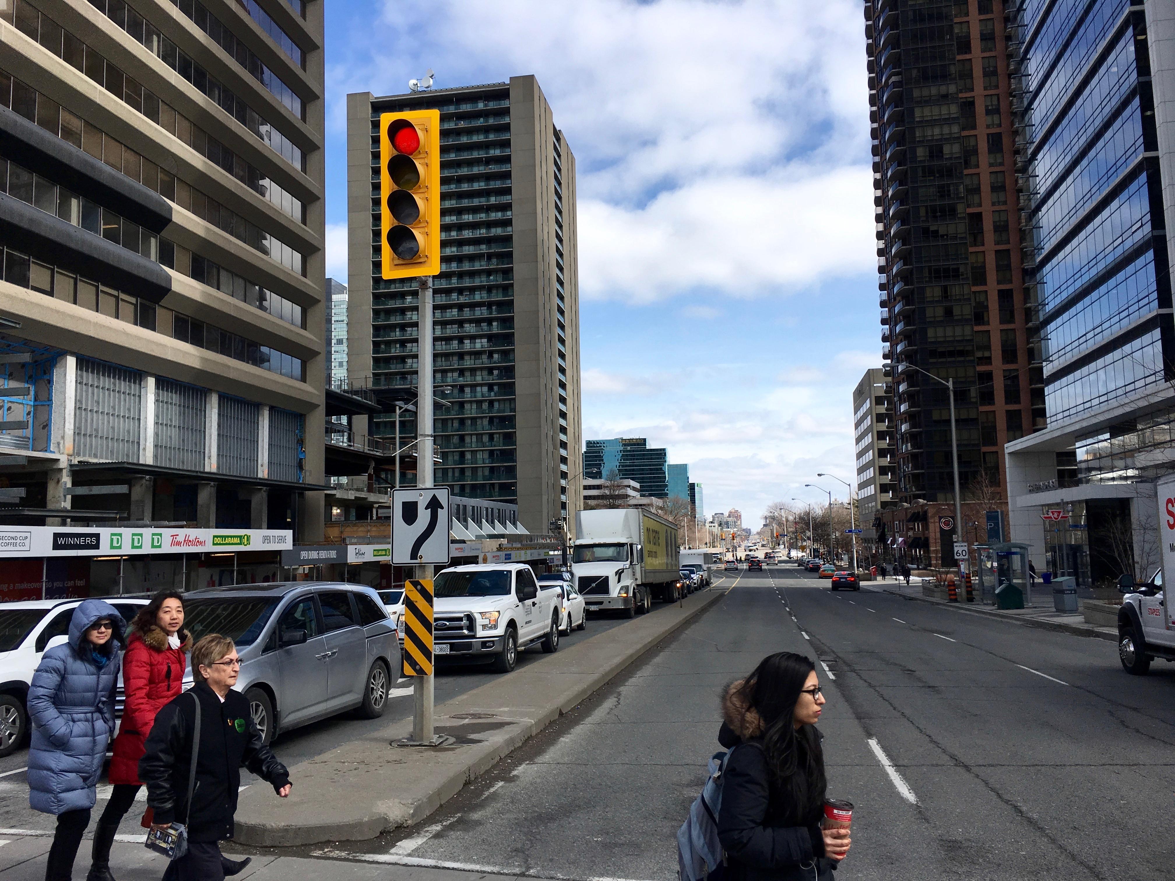 12:01 p.m., March 2, 2018. Pedestrians cross Sheppard Avenue, east of Yonge, where Doris Avenue starts.