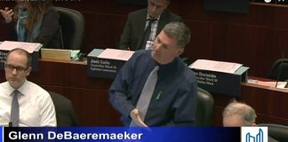 """Screen capture from the March 2018 city council meeting. Councillor Glenn De Baeremaeker points to Councillor John Campbell during his remarks on the council debate on cryptocurrency. """"When I want something dumbed down to the simplest level, I go to Councillor Campbell. Councillor Campbell and I have been sitting here with our iPads, thinking of everything we can to dumb it down to its simplest level,"""" Glenn De Baeremaeker said."""