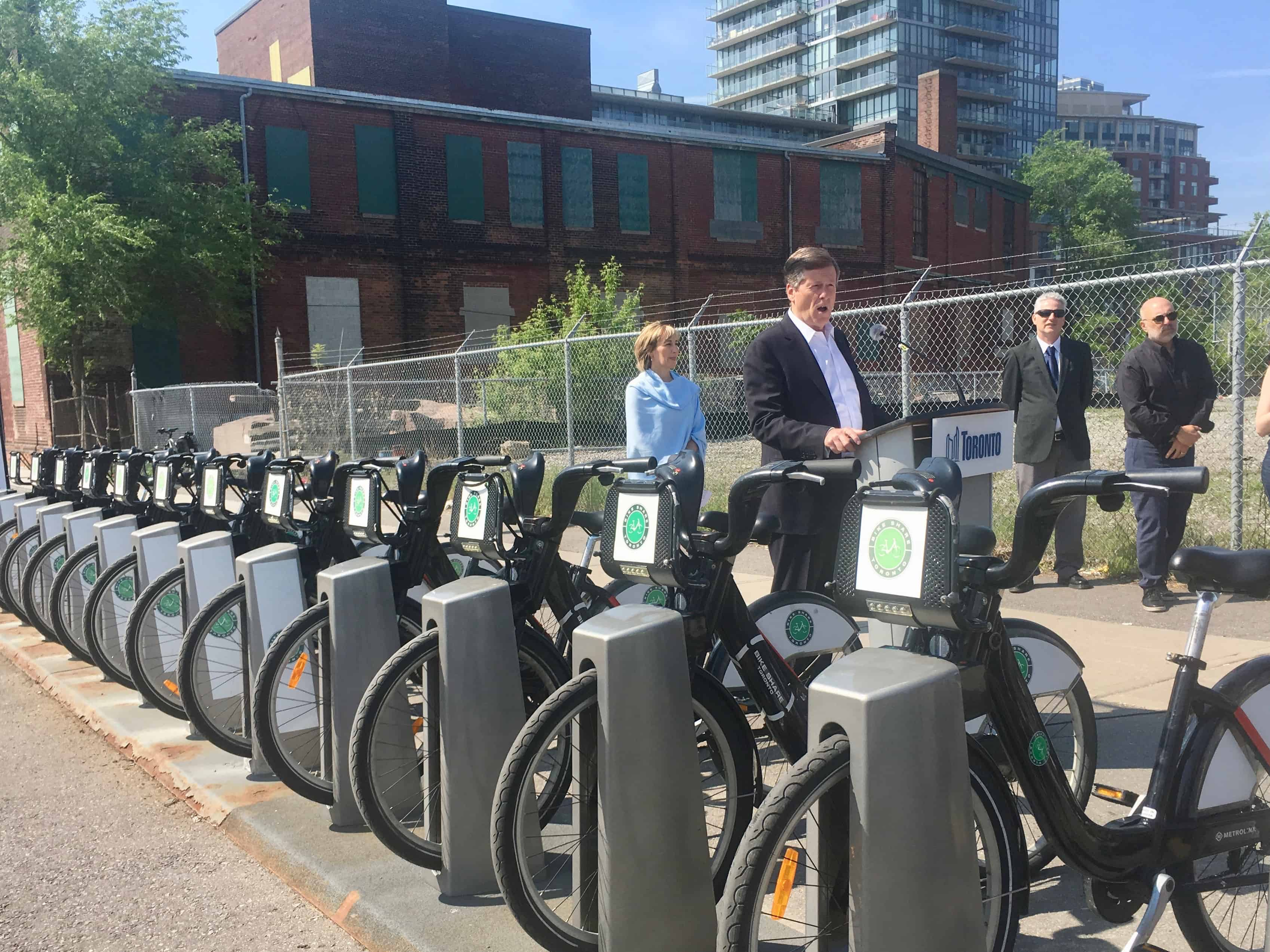 10:22 a.m., May 30, 2018. Mayor John Tory speaking at announcement for Bike Share free half-hour rides on Wednesdays in June. Rhonda English, Chief Marketing Officer at CAA, looks on.