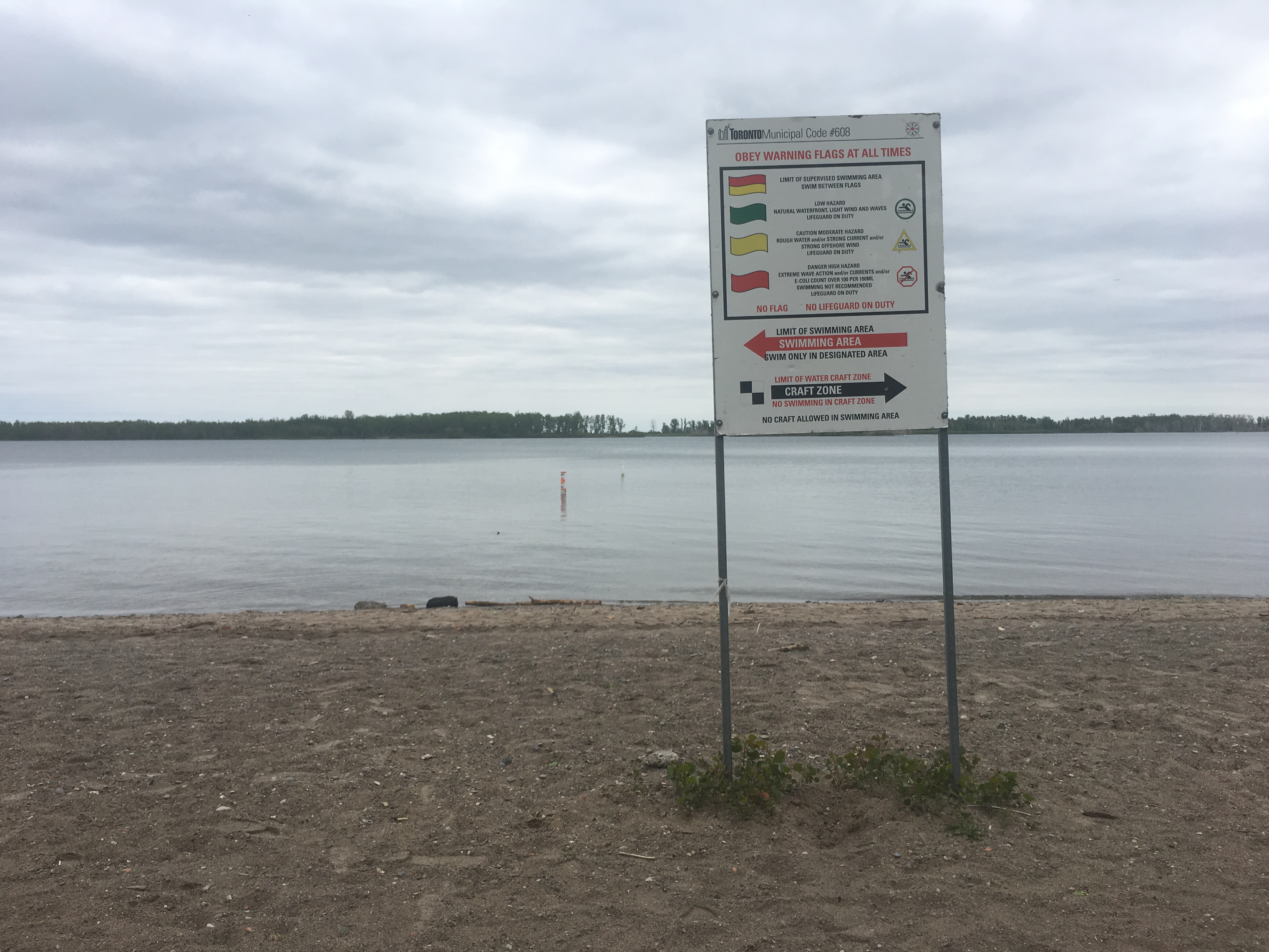"""2:13 p.m. June 5, 2018. On Tuesday, one beach sign tells visitors to """"Obey Warning Flags at all times"""" and """"no flag... no lifeguard on duty,"""" nearby the station where lifeguards sat."""