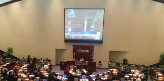 4:13 p.m. July 30, 2018. Councillors Mark Grimes (sitting) and Justin Di Ciano (standing) shown on the council chambers screen at council's last regular meeting.
